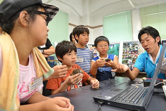 2013年7月20日(土)、公募によって集められた小学生の子供たち20名が参加したミキモトの「真珠の学校」が開校!磯での生物採集や海、真珠についてのレクチャー、そして真珠を育むアコヤ貝への「核入れ」を体験!子供たちからはたくさんの笑顔と真剣な顔が見られました!
