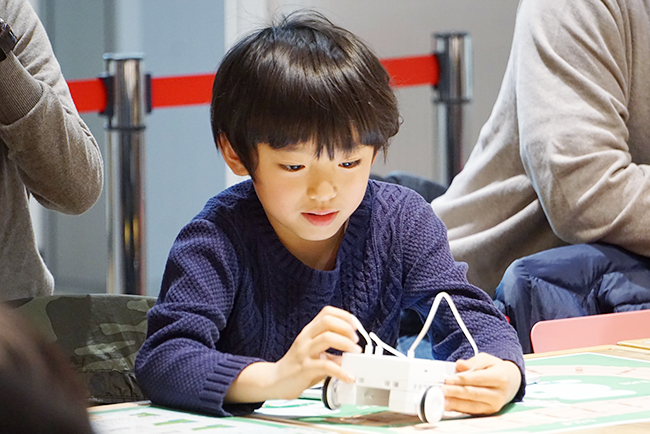 ソニーの体験型科学館「ソニー・エクスプローラサイエンス」(東京・お台場)では、玩具としても教材としても楽しめるロボット・プログラミング学習キット「KOOV®」(クーブ)のワークショップを2019年5月11日(土)、12日(日)の2日間開催!子供たちは事前に組み立てられた「列車」を紙の線路に合わせ、「まっすぐ走ったあと、曲がる」「○○駅で止める」といった、モーターを制御する初歩的なプログラミングに挑戦します。