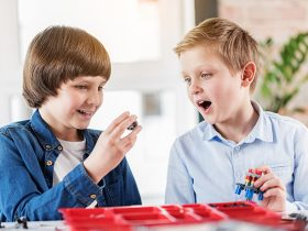 Surprised boy is looking at detail, his friend showing to him. They sitting near table in workshop